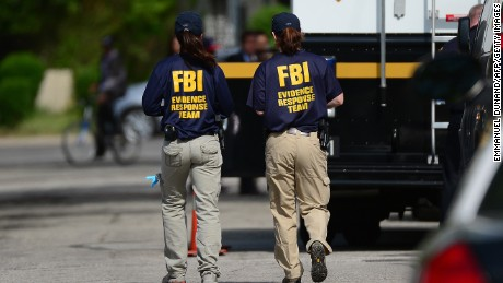 FBI forensic personnel walk in front of the house where three women were held captive for a decade on May 7, 2013 in Cleveland, Ohio.
