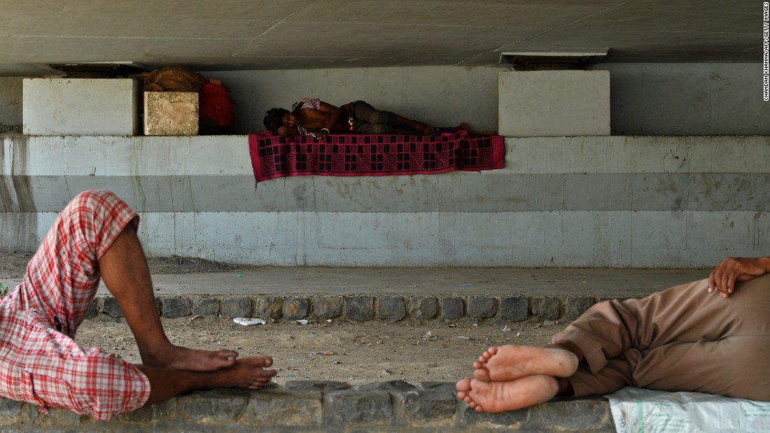 Men sleep in the shade under a bridge in New Delhi on May 27.