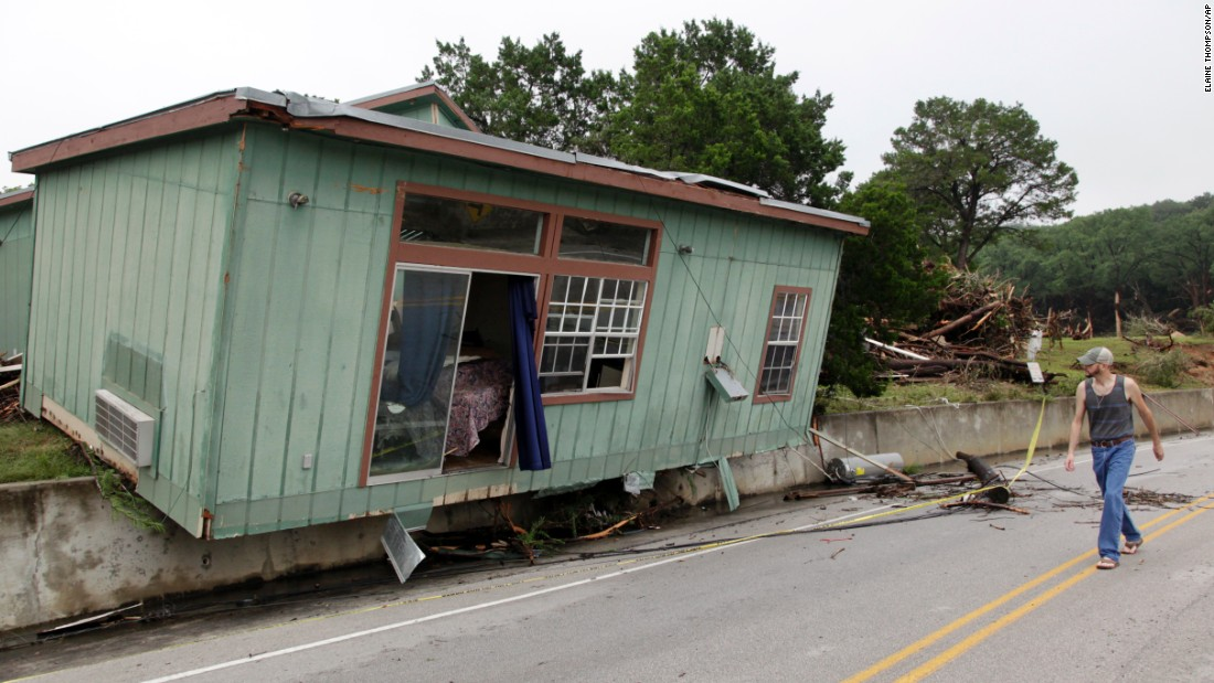 On Tuesday, May 26, a Wimberley man walks past a cabin that was torn from its foundation days earlier.