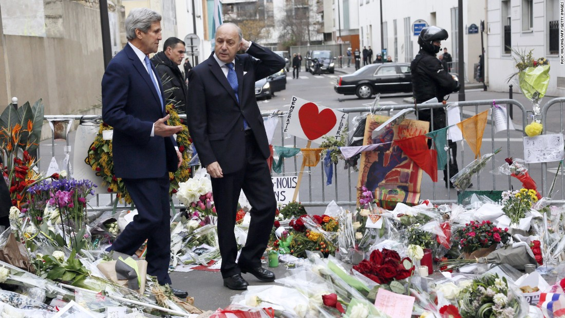 Kerry walks with French Foreign Minister Laurent Fabius in Paris on January 16 through a memorial to the victims killed in the attack on the satirical newspaper Charlie Hebdo.