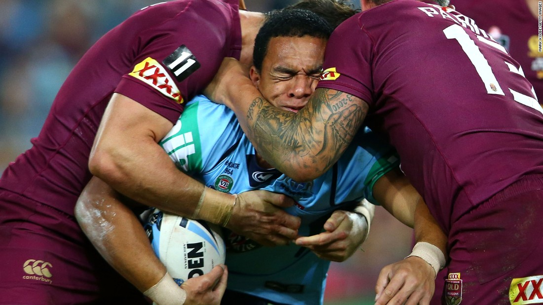 Rugby player Will Hopoate, of the New South Wales Blues, is tackled by Queensland Maroons during Game 1 of the State of Origin series Wednesday, May 27, in Sydney. Queensland won 11-10 to take the early lead in the best-of-three series.