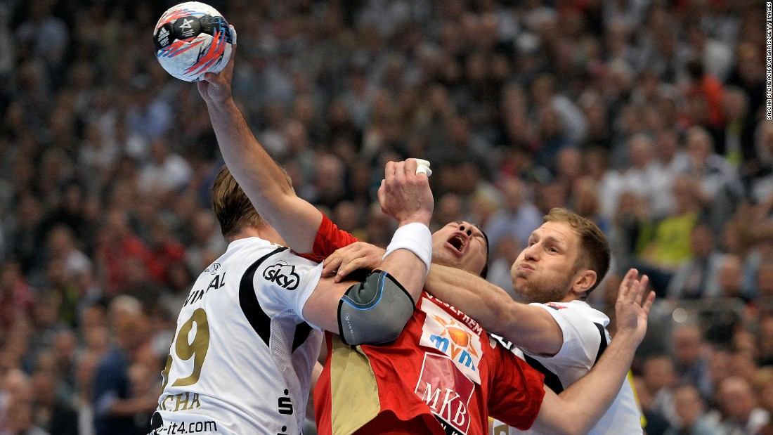 Veszprem handball player Jose Maria Rodriguez Vaquero is tackled by Kiel players on Saturday, May 30, during the semifinals of the Champions League in Cologne, Germany.
