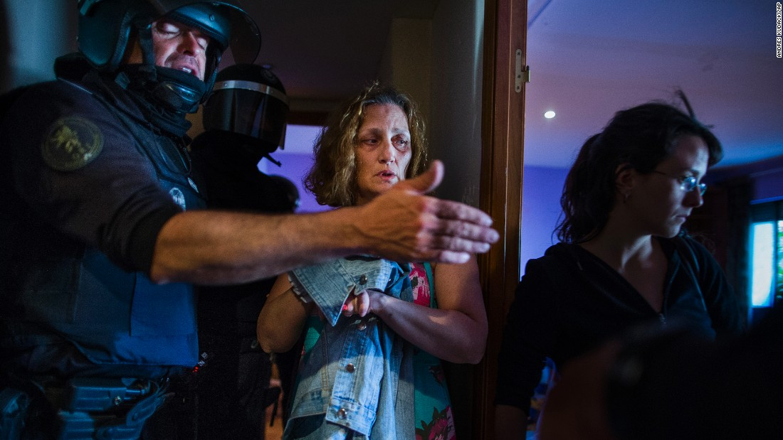 Police enter the Madrid apartment of Carmen Rives, center, to evict her on Tuesday, June 2. The eviction was carried out by dozens of police officers who also arrested at least 12 anti-eviction activists. Evictions in Spain have soared since the country's economic crisis began in 2008, and protesters regularly try to prevent them.