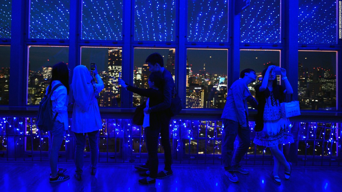 Visitors of Tokyo Tower take photographs under LED lights representing the Milky Way on Monday, June 1.
