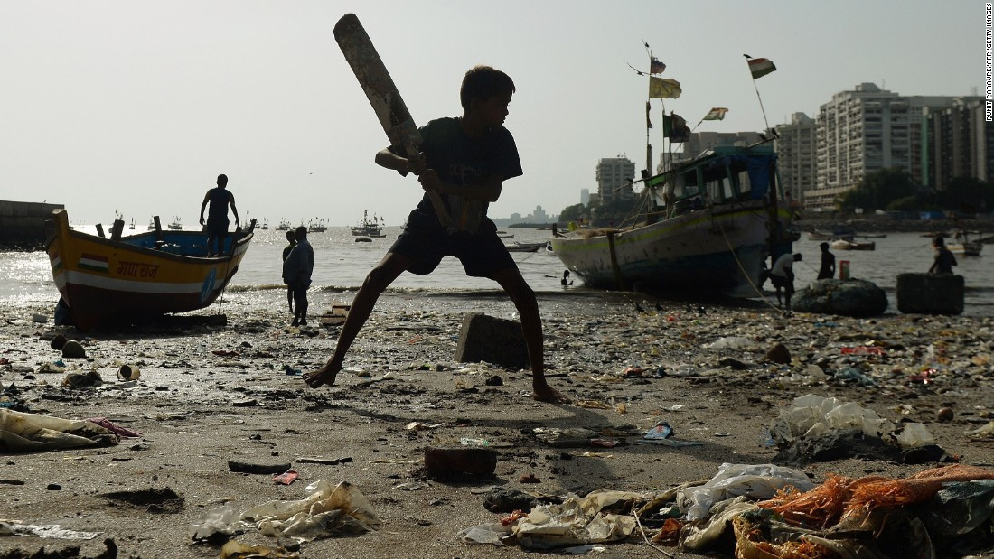 A boy plays cricket on a garbage-covered beach in Mumbai, India, on Wednesday, June 3.