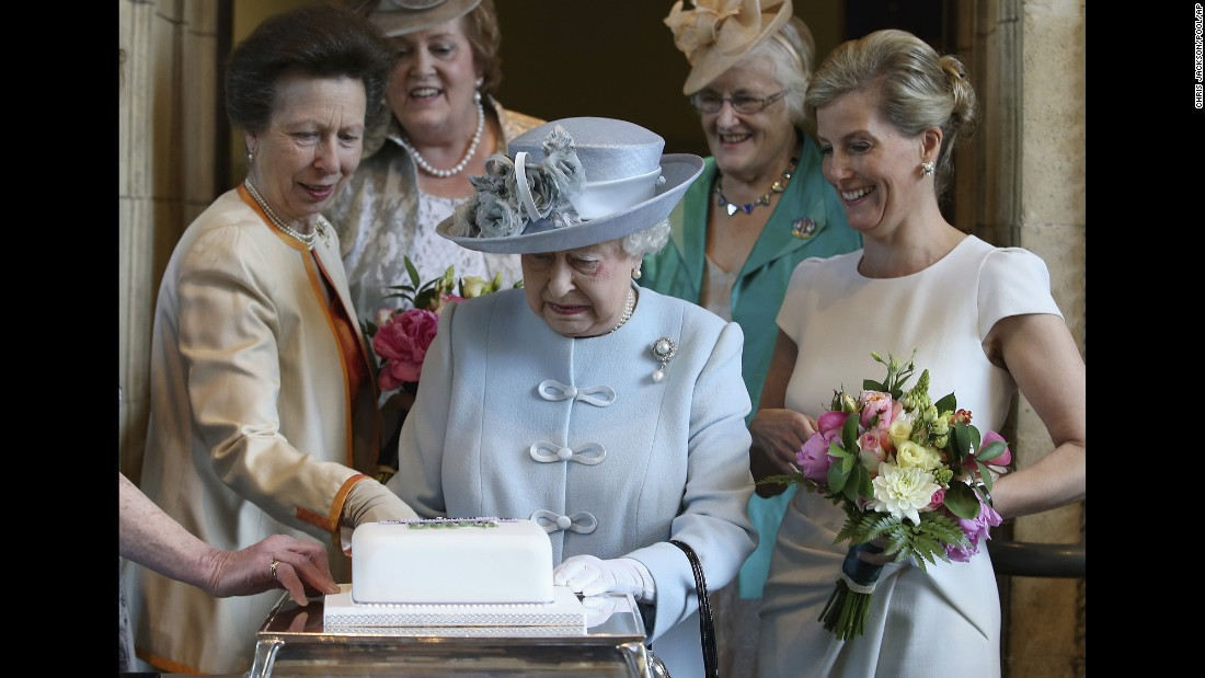 "Britain's Queen Elizabeth II, center, prepares to cut a cake in London on Thursday, June 4, during the 100th annual meeting of the <a href=""http://www.thewi.org.uk/about-the-wi"" target=""_blank"">National Federation of Women's Institutes</a>. On the left is Elizabeth's daughter, Princess Anne, and on the right is Elizabeth's daughter-in-law Sophie, Countess of Wessex."