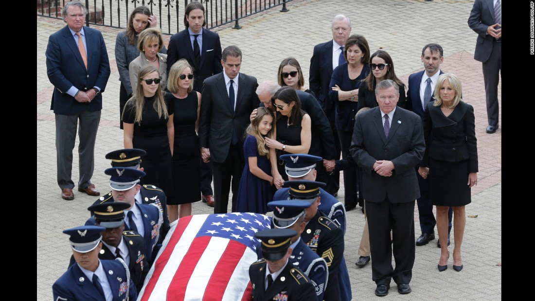 Natalie Biden, center, is comforted by her grandfather and her mother as they follow the honor guard carrying the casket.