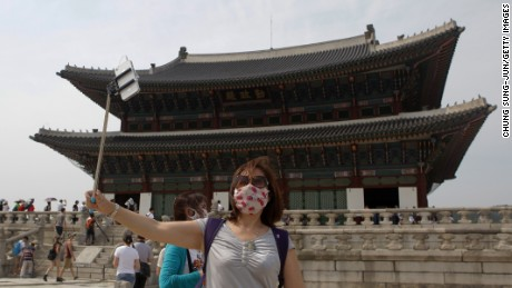 SEOUL, SOUTH KOREA - JUNE 04: A woman wears mask as a precaution against the MERS virus at the Gyeongbok palace on June 4, 2015 in Seoul, South Korea. Two deaths from Middle East Respiratory Syndrome (MERS) have been confirmed on June 2, 2015, and the number of confirmed local patients have risen to 35 as of June 4, 2015. More than 700 schools from kindergartens to colleges have been closed. (Photo by Chung Sung-Jun/Getty Images)
