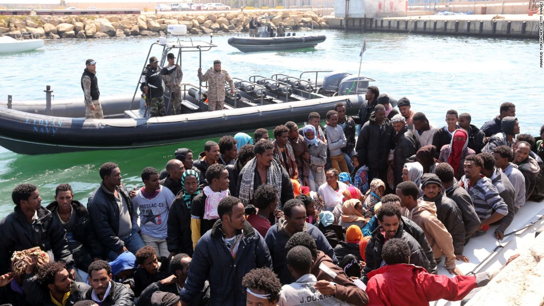 Libyan coast guard personnel watch over migrants after the Libyan navy escorted their vessel to the capital, Tripoli, on June 6.