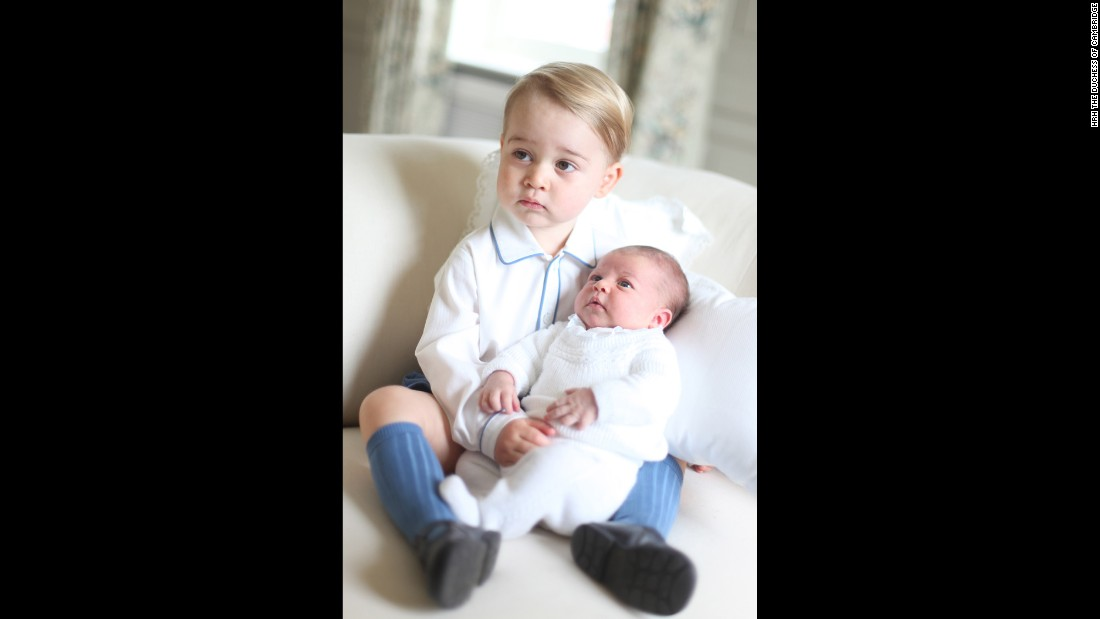 George holds his baby sister, who was only a couple weeks old when photographed. The release of the images comes a day after the palace announced that Charlotte, who's fourth in line to the throne, would be christened on July 5.