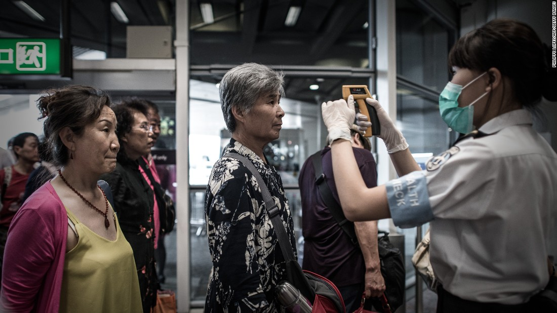 Passengers get their temperatures checked as part of preventive measures against the spread of MERS at the Hong Kong International Airport on June 5.