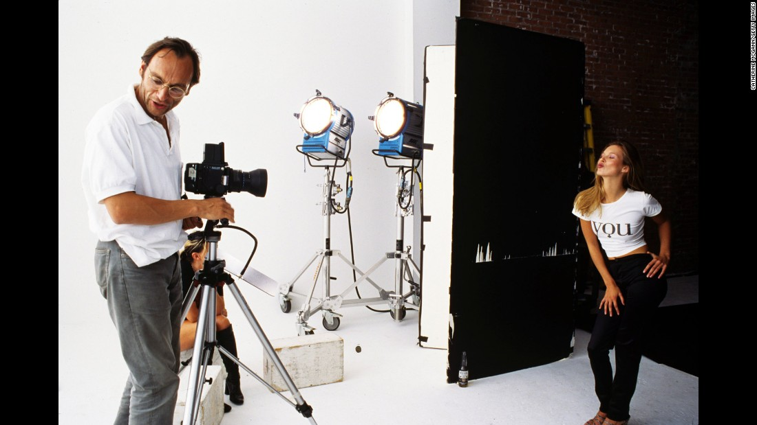 Photographer Kim Knott stands at his camera addressing an assistant as Moss strikes a pose during a 1995 shoot in New York City.