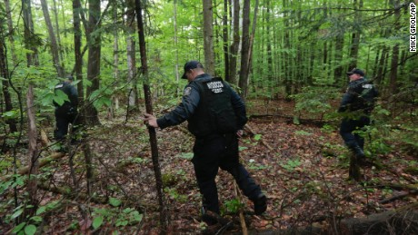 Members of the New York State Department of Corrections and Community Supervision emergency response team search a wooded area for two prisoners who escaped from the Clinton Correctional Facility on Monday, June 8, 2015, in Dannemora, N.Y. The two murderers who escaped from the prison by cutting through steel walls and pipes remain on the loose Monday as authorities investigate how the inmates obtained the power tools used in the breakout. (AP Photo/Mike Groll)