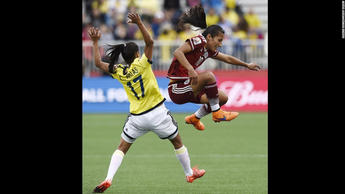 Mayor jumps next to Colombian midfielder Carolina Arias.