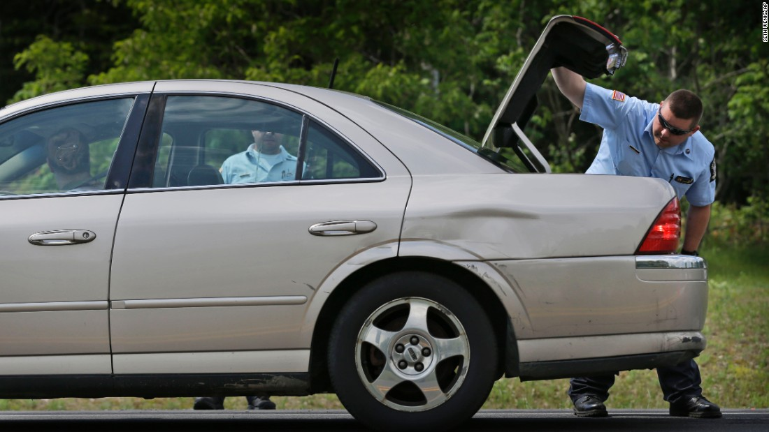 An officer checks the trunk of a car at a checkpoint near the Dannemora border on June 10.