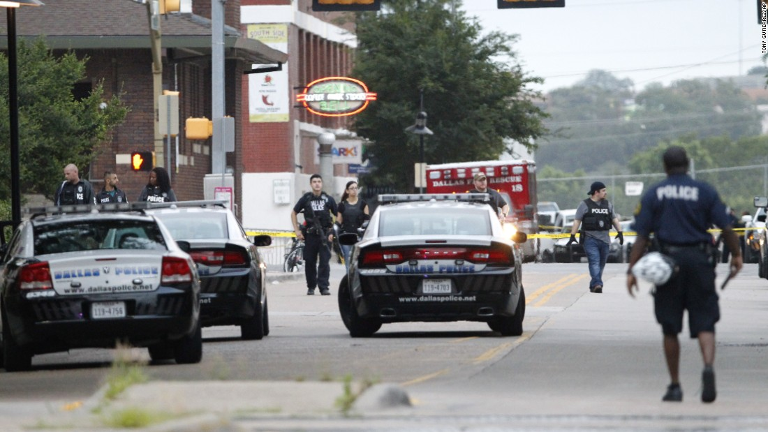 Dallas police officers search Belleview Street near the headquarters.