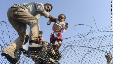 Syrians break through border fence fleeing violence