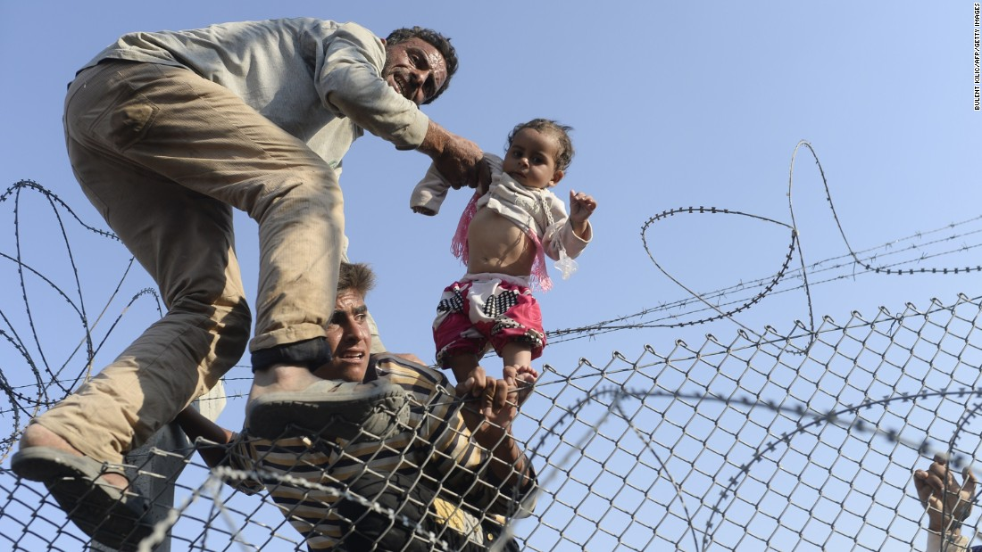 "A child is lifted over the fence. AFP photographer Bulent Kilic, who was at the crossing, described the scene as unprecedented in his years of covering the conflict. ""They just came inside with their children, with their babies. I can say it's incredible,"" he told CNN."