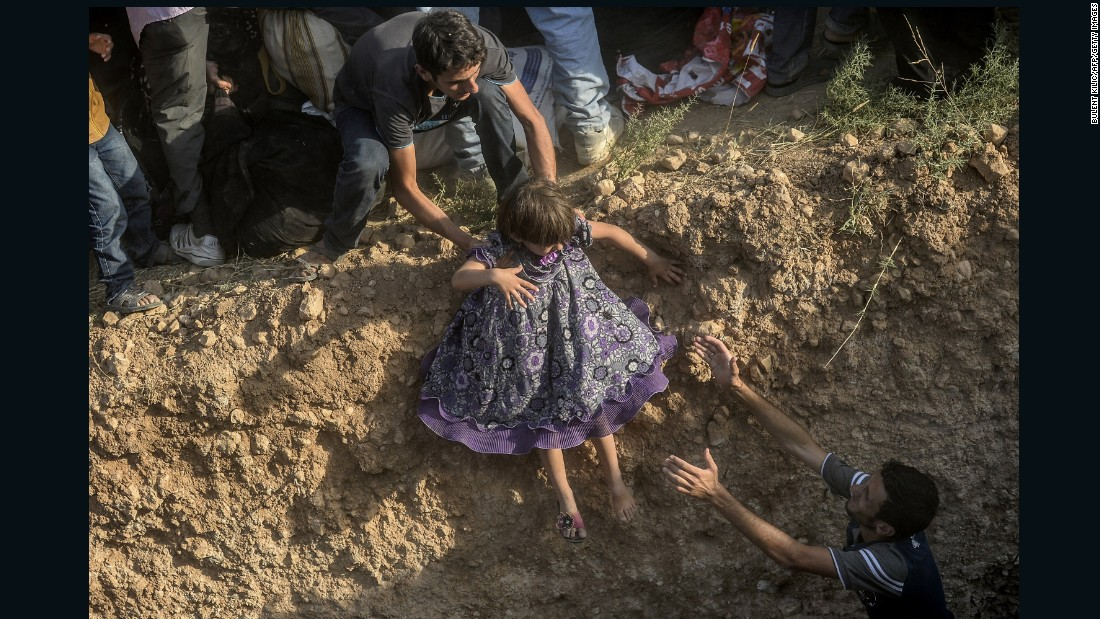 "A young girl is helped in crossing a ditch near the border. Photographer Bulent Kilic told CNN that the Turkish military initially fired warning shots in the air as the refugees tried to cross, but then ""they didn't do anything. They took all the people, let's say thousands of them, inside Turkey."""