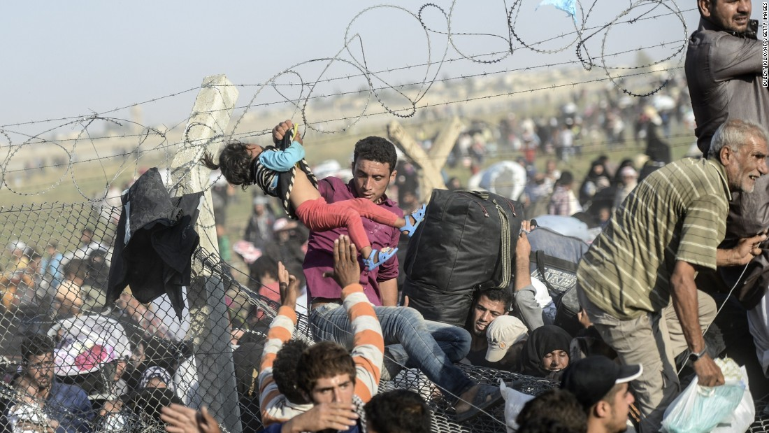 A man carries a young girl as they flee through the broken border fence to enter Turkey.