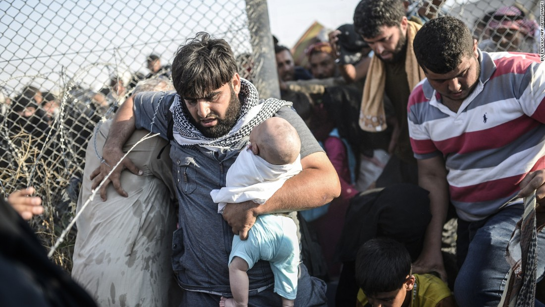 "A man crosses through the fence carrying a baby. Under an ""open-door"" policy, Turkey has taken in 1.8 million refugees since the conflict in Syria erupted in 2011."