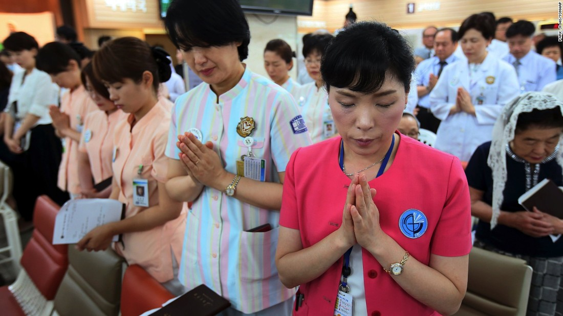 Hospital workers pray as they attend a special service for patients suffering from MERS, at a Sungmo hospital in Seoul, South Korea on Friday, June 12, 2015.