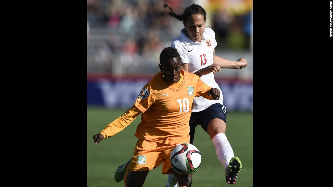 Ivory Coast forward Ange Nguessan, left, holds off Norway defender Ingrid Moe Wold.