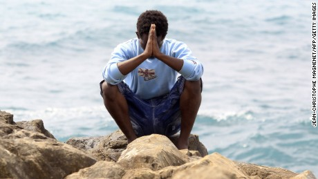 A migrant prays next to the sea in the city of Ventimiglia, Italy.