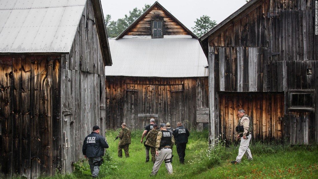 A task force of U.S. Marshals and police officers go door to door near Dannemora, New York, searching for the two escaped murderers on Tuesday, June 16.