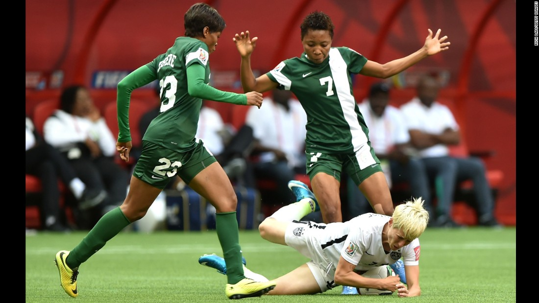 Megan Rapinoe of the United States is knocked down by Ngozi Ebere, left, and Ukpong Sunday of Nigeria.