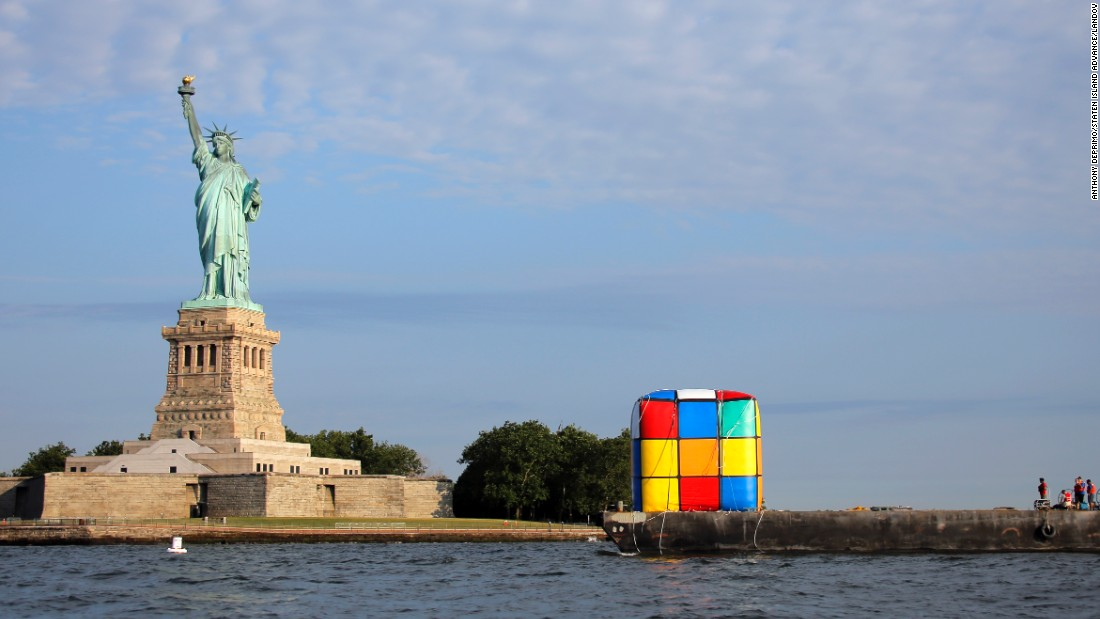 An inflatable Rubik's Cube, en route to a science museum, is transported past the statue in July.