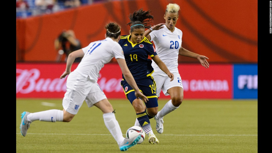 Leicy Santos of Colombia tries to move the ball past England defenders.