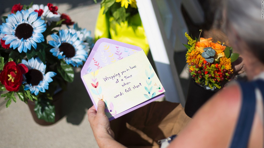 Sandra Bridges lays a card at a memorial on June 18.