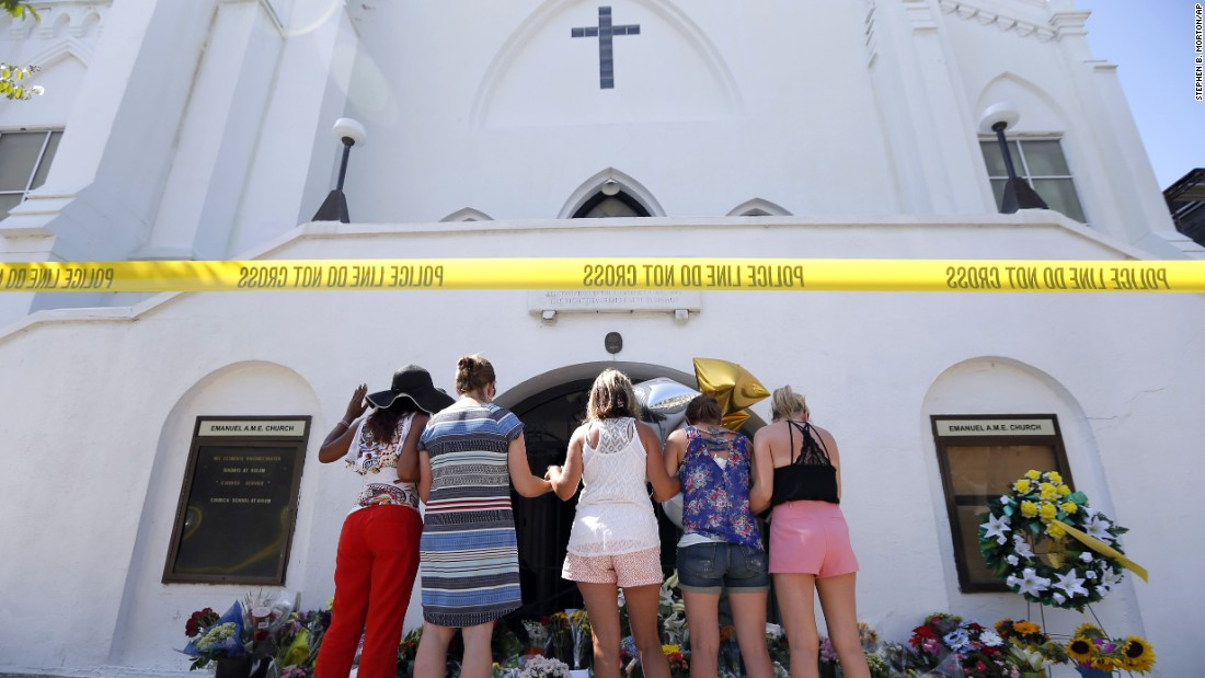 A group of women prays together at a makeshift memorial on the sidewalk in front of the Emanuel AME Church on June 18.