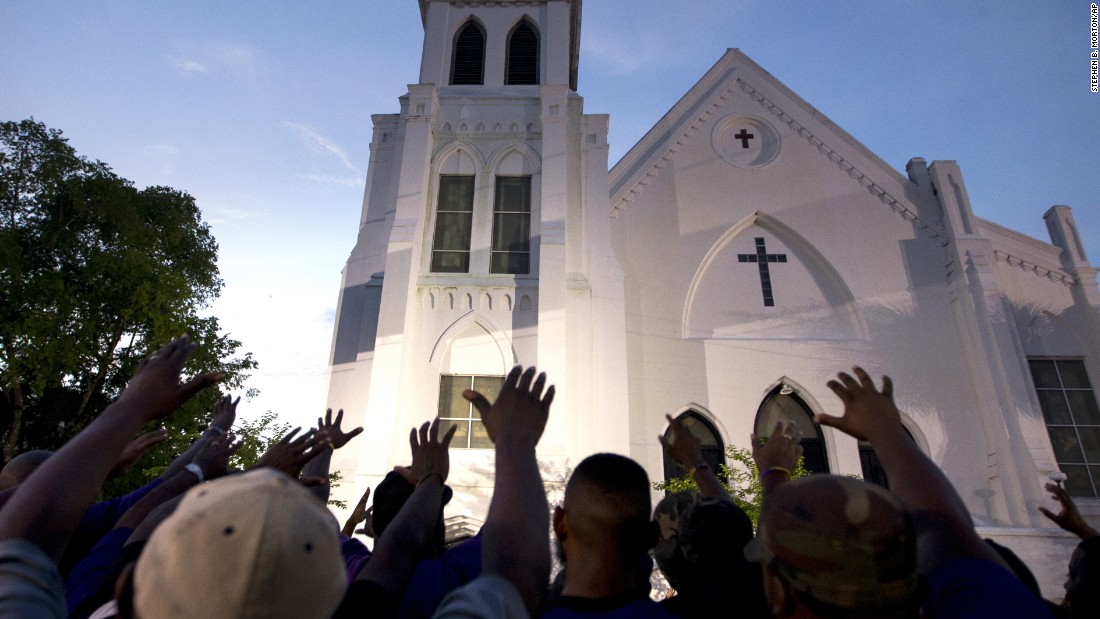 The men of Omega Psi Phi Fraternity lead a prayer outside Emanuel AME Church, Friday, June 19.