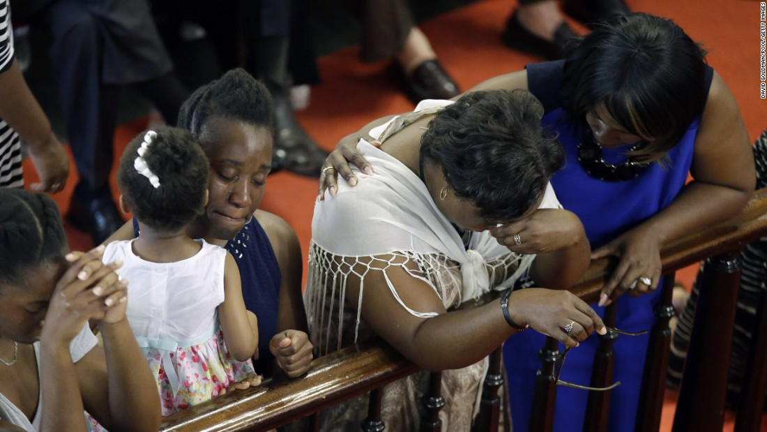 Parishioners pray and comfort each other during the service.