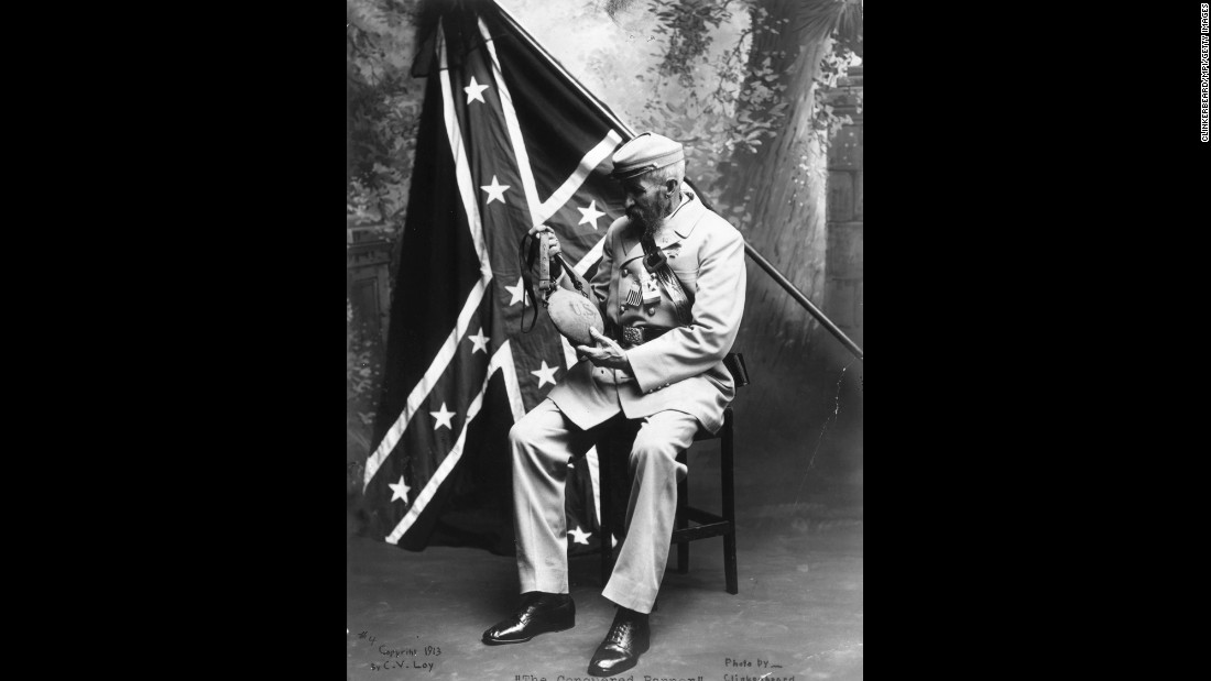 A veteran of the Confederate States of America examines a Union water bottle in front of a Confederate flag. Here's a look at the evolution of that flag.