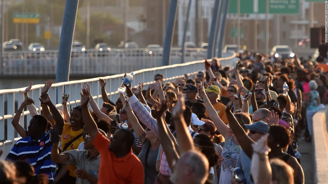 "Thousands of people march on the Arthur Ravenel Jr. Bridge in Charleston, South Carolina, on Sunday, June 21.  People crossed the bridge, which spans the Cooper River, from Mount Pleasant to Charleston, joining hands in a unity chain to mourn the Emanuel AME Church shooting. Police arrested Dylann Storm Roof in the slayings of <a href=""http://www.cnn.com/2015/06/18/us/gallery/charleston-south-carolina-church-shooting/index.html"" target=""_blank"">nine people </a>at a prayer meeting at the church."