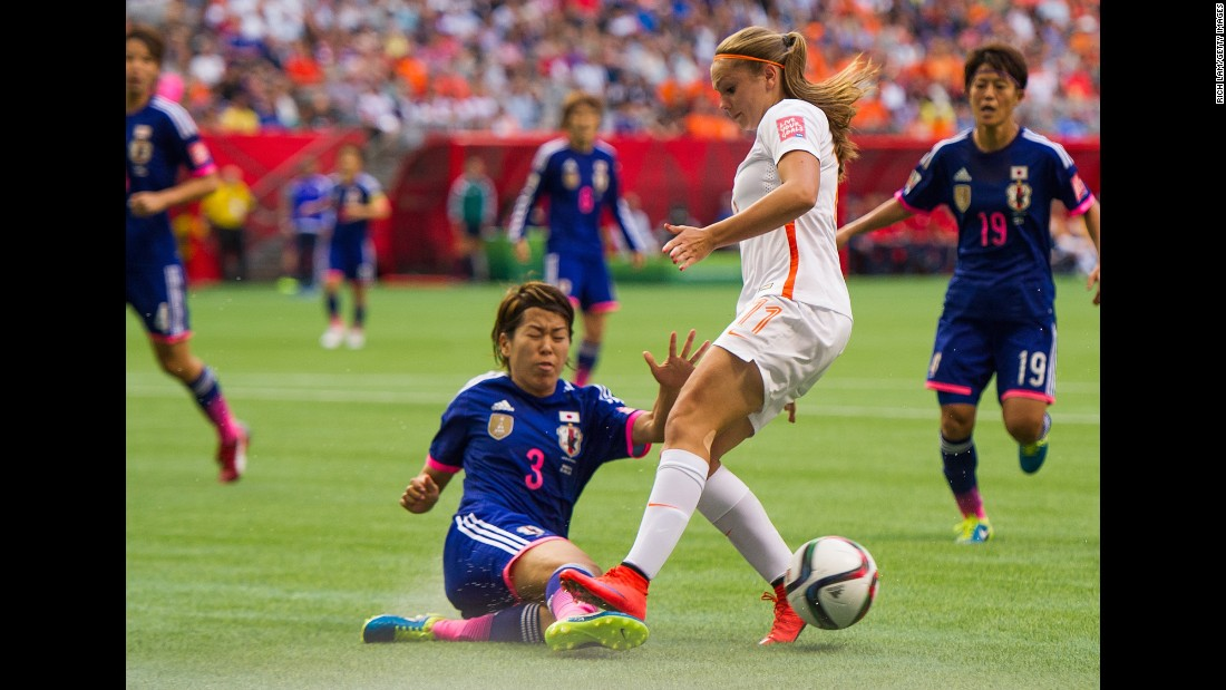 Japan's Azusa Iwashimizu knocks the ball away from Lieke Martens.
