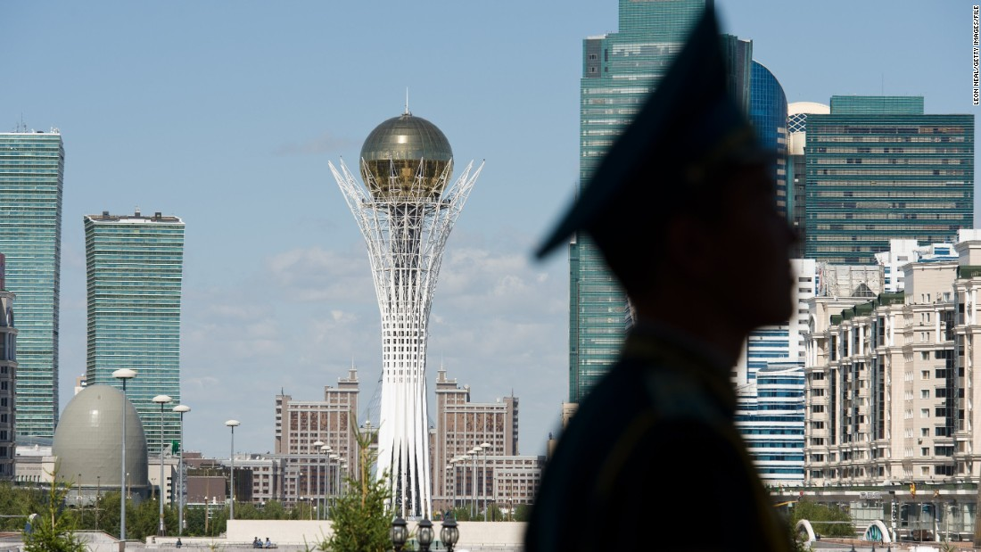 The Bayterek Tower, a monument and viewing tower, is visible in the center of Astana as a soldier stands guard.