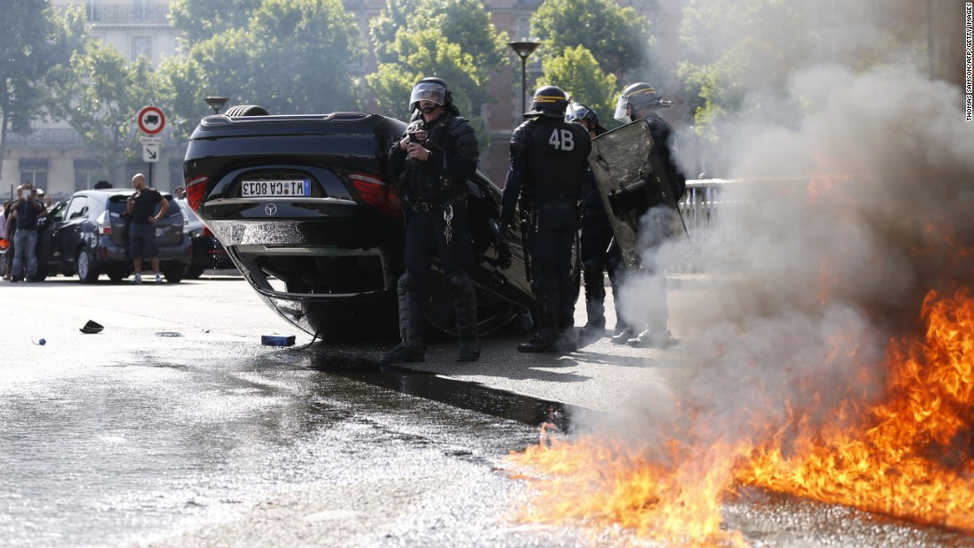 A fire burns next to riot police and an overturned car in Paris on June 25.