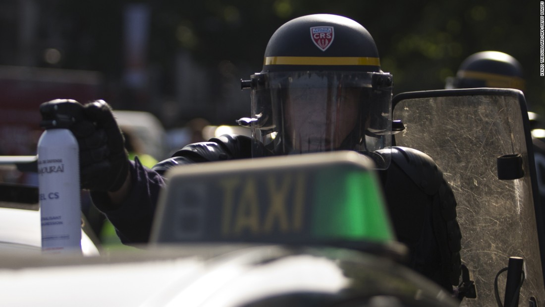 A police officer holds up a can of tear gas as taxi drivers block the Porte Maillot Métro station in Paris on June 25.