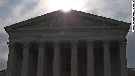 The early-morning sun rises behind the Supreme Court building in Washington on  June 18, 2015.
