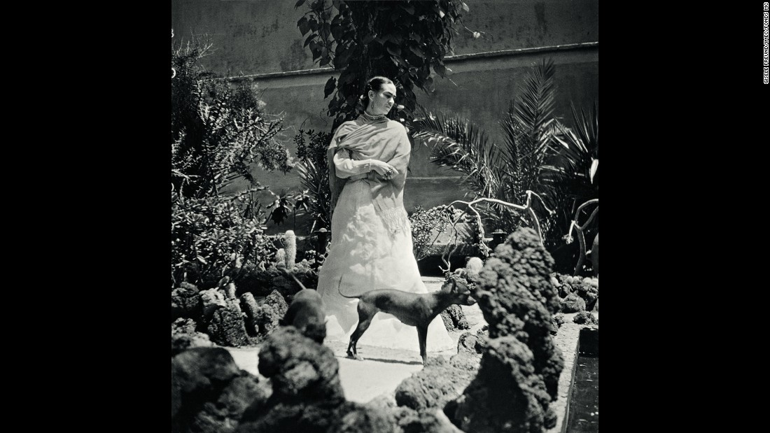 Kahlo stands in her garden with her dogs in 1951.