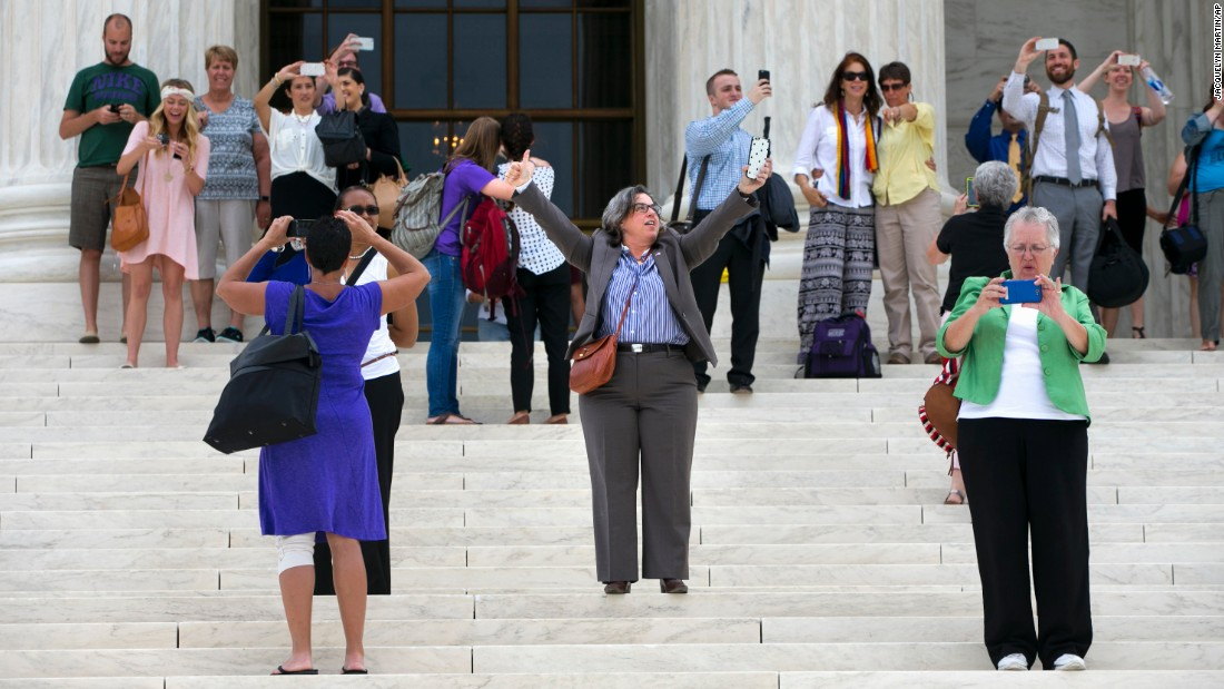 Chris Svoboda, president of the Virginia Equality Bar Association, raises her arms in victory on the steps of the Supreme Court on June 26.