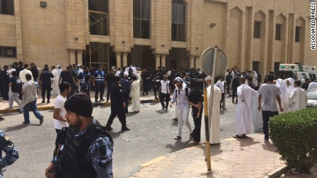 Security forces, officials and civilians gather outside of the Imam Sadiq Mosque after a deadly blast struck after Friday prayers in Kuwait City, Kuwait, Friday, June 26, 2015. There was no immediate claim of responsibility for what appears to be a bombing that targeted the Shiite mosque.