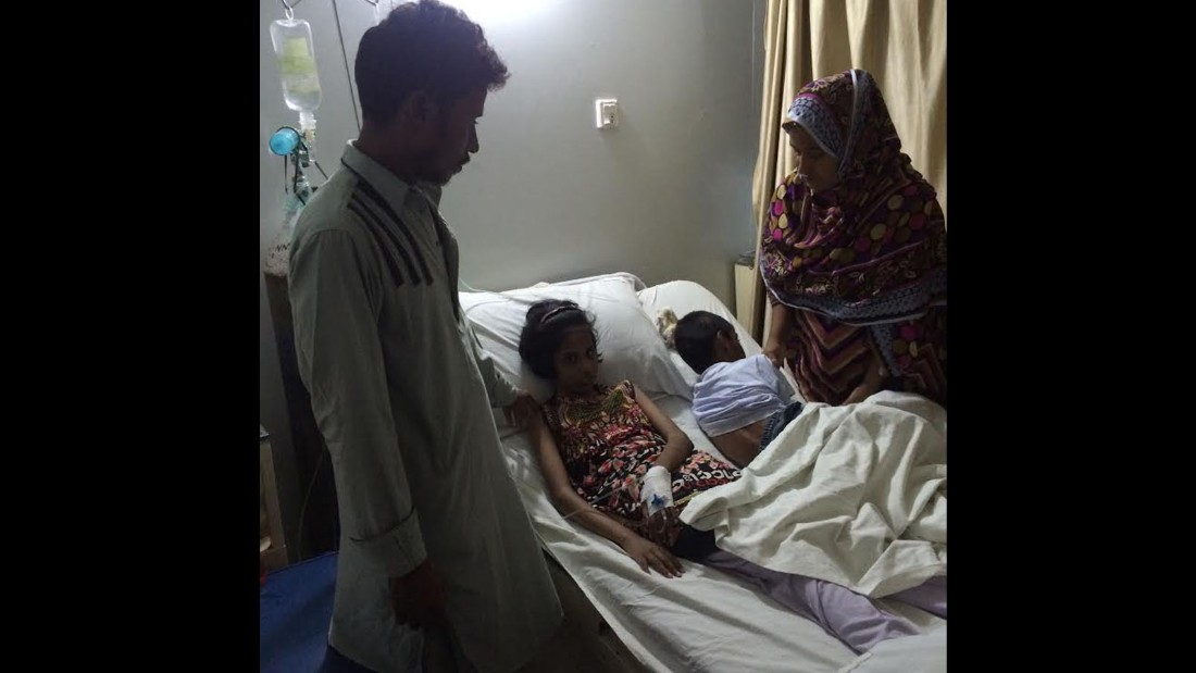 Sameer's wife Husna holds vigil by her children's bedside. They are depending on charity to continue keeping them in the hospital.