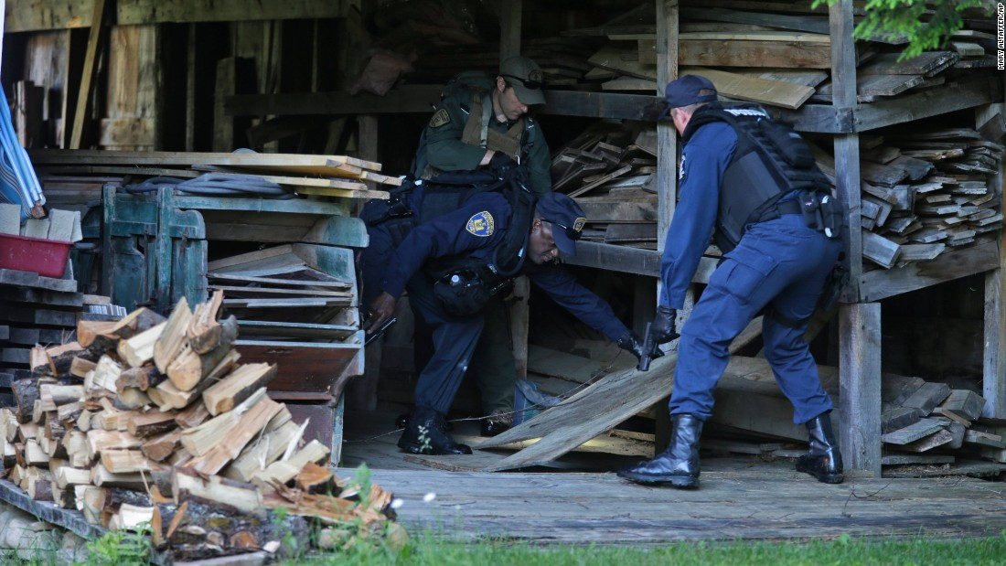 Department of Corrections officers and a forest ranger, back, search a barn in Owls Head, New York, on June 26.