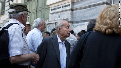 A pensioner reacts as he listens from a bank employee that he is not going to receive his pension after waiting for hours outside the National bank of Greece headquarters in Athens, Monday, June 29, 2015. Anxious Greek pensioners swarmed bank branches hoping to be able to receive their pensions Monday and others lined up at ATMs as they gradually began dispensing cash again on the first day of capital controls imposed in a dramatic twist in Greece's five-year financial saga. (AP Photo/Petros Giannakouris)