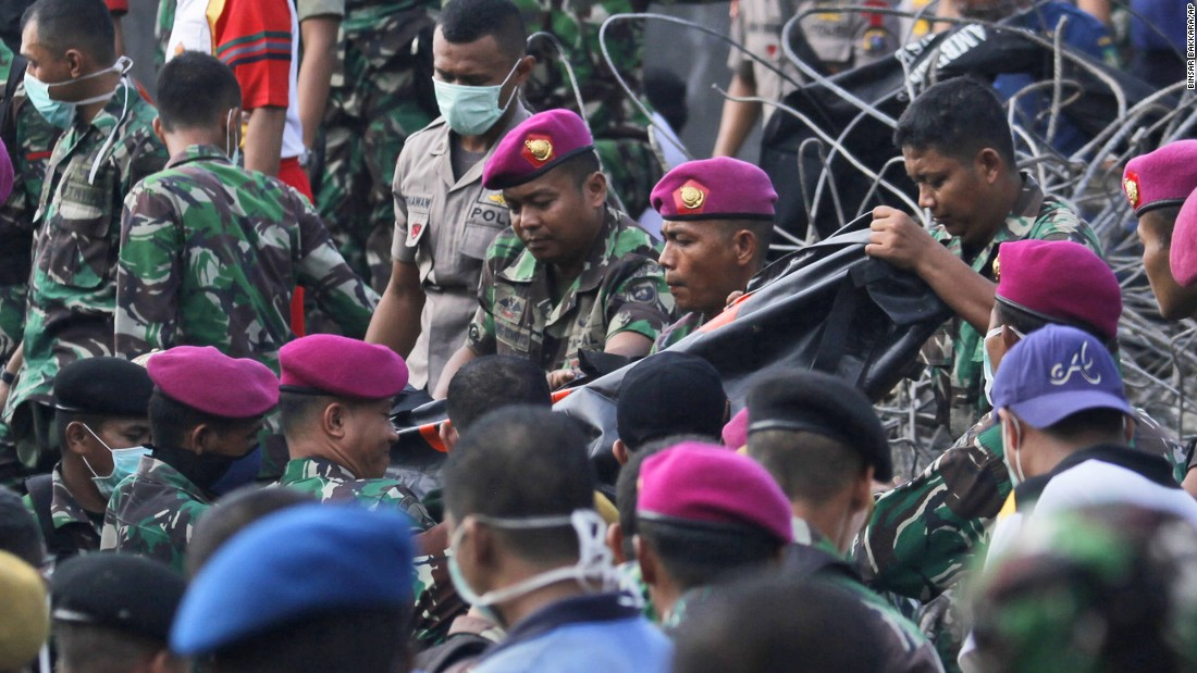 Indonesian military personnel carry the body of a victim away from the crash site.